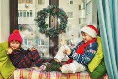 Lustige Kinder mit Wunderkerzen Bruder und Schwester in Sankt-Hüten lizenzfreie stockfotos