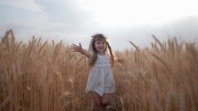 Lustige Kindheit, süßes kleines Mädchen mit schönen blauen Augen in den weißen Kleidungsläufen mit den Armen verbreitet über Feld stock video