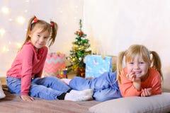 Lustige kleine Mädchen lachen und sprechen und werfen auf Boden an liegen und auf Stockfotos