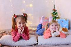 Lustige kleine Mädchen lachen und sprechen und werfen auf Boden an liegen und auf Stockbilder