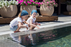 Lustige kleine Mädchen (Schwestern) spielen nahe dem Pool Lizenzfreie Stockfotografie