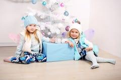 Lustige kleine Mädchen, die neben einem verzierten Weihnachtsbaum aufwerfen Stockbild