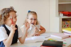 Lustige kleine Schüler sitzen bei einem Schreibtisch Lizenzfreie Stockbilder