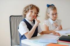 Lustige kleine Schüler sitzen bei einem Schreibtisch Stockfoto