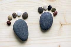 Lustige kleine Steinfüße und zehn Zehen auf hölzernem Hintergrund, Stein in Form menschlichen Füße Stockbilder