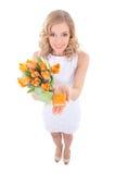Lustige lächelnde Frau mit orange Tulpen und wenigem Geschenkbox isola Lizenzfreie Stockfotos