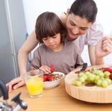Lustige Mutter und ihr Kind, die frühstückt stockbilder