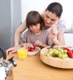 Lustige Mutter und ihr Kind, die frühstückt Lizenzfreies Stockfoto