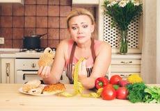 Lustige nährende Frauenhausfrau, die zwischen gesundem Lebensmittel wählt und stockfotos