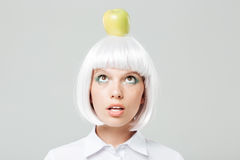 Lustige nette junge Frau mit Apfel auf ihrem Kopf Stockfotografie