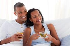 Lustige Paare, die eine Tasse Tee auf ihrem Bett trinken Stockfotografie