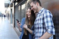 Lustige Paare, die intelligenten Telefoninhalt in der Stra?e ?berpr?fen stockfotos