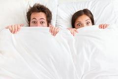 Lustige Paare im Bett Lizenzfreie Stockfotografie
