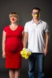 Lustige Paare mit lustigen Wekzeugspritzen und Blumenstrauß Lizenzfreies Stockbild