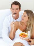 Lustige Paare, welche die Frucht liegt auf ihrem Bett essen lizenzfreies stockfoto