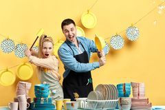 Lustige positive Paare in den Schutzblechen, die Spaß während des Handelns der Hausarbeit und des Säuberns haben stockfoto