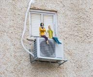 Lustige Puppe, die auf der Klimaanlage sitzt Stockbilder