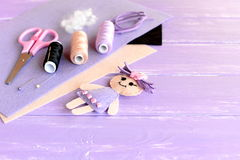 Lustige Puppe verziert mit Knöpfen, Threadsatz, Nadel, Stifte, Scheren, flache Stücke Filz auf hölzernem Hintergrund mit leerem P stockfotos