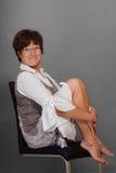Lustige reife Frau auf Stuhl barfuß Stockfoto