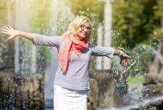 Lustige reife Mitte gealterte lächelnde blonde Frauen-tragende Schauspiele, die draußen im Park aufwerfen Stockbild