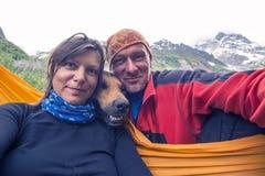 Lustige Reisende mit dem großen lächelnden Hund, selfie auf dem Berg nehmend Lizenzfreies Stockbild