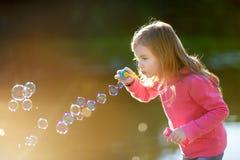 Lustige reizende Schlagseifenblasen des kleinen Mädchens Stockbilder