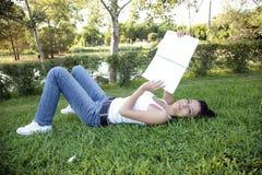 Lustige schöne Jugendliche, die auf Gras sitzt stockfoto