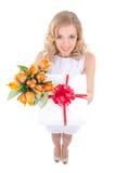 Lustige Schönheit, welche die Geschenkbox und Blumen lokalisiert auf w hält Stockfotos