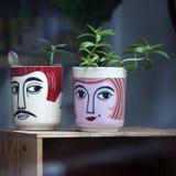 Lustige Schalen mit den männlichen und weiblichen Gesichtern im Shopfenster für Verkauf Lizenzfreie Stockfotos