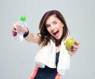 Lustige sportliche Frau, die Apfel und Flasche mit Wasser hält Stockfotos