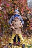 Lustige und glückliche Kinder werden vor dem hintergrund der gelben Blätter des Herbstes gespielt stockfoto