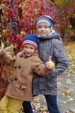 Lustige und glückliche Kinder werden vor dem hintergrund der gelben Blätter des Herbstes gespielt lizenzfreies stockfoto