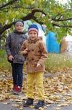 Lustige und glückliche Kinder werden vor dem hintergrund der gelben Blätter des Herbstes gespielt lizenzfreie stockfotografie
