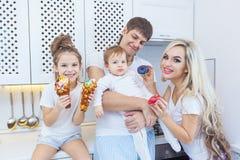 Lustige vierköpfige Familie auf dem Hintergrund der hellen Küche schön haben den Spaß, der Schaumgummiringe herum essen täuscht D Lizenzfreie Stockbilder
