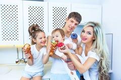 Lustige vierköpfige Familie auf dem Hintergrund der hellen Küche schön haben den Spaß, der Schaumgummiringe herum essen täuscht D Lizenzfreie Stockfotografie