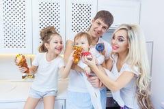 Lustige vierköpfige Familie auf dem Hintergrund der hellen Küche schön haben den Spaß, der Schaumgummiringe herum essen täuscht D Stockbilder