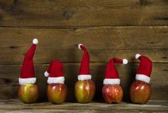 Lustige Weihnachtsgrußkarte mit fünf roten Sankt-Hüten auf Äpfeln Stockbild