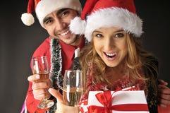 Lustige Weihnachtspaare mit Gläsern Champagner. stockfoto