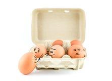 Lustige Zeichnungs-Gesichter auf Eiern im Karton mit Beschneidungspfad Stockfotografie