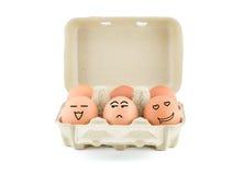 Lustige Zeichnungs-Gesichter auf Eiern im Karton mit Beschneidungspfad Lizenzfreies Stockfoto
