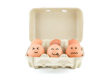 Lustige Zeichnungs-Gesichter auf Eiern im Kartonisolat auf Weiß mit Klipp Stockbilder