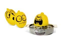Lustige Zitrone, die auf Weiß zusammendrückt Stockfotos