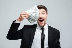 Lustiger aufgeregter junger Geschäftsmann bedeckte ein Auge mit Geld Lizenzfreie Stockfotografie