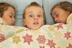 Lustiger Ausdruck auf Jungengesicht zwischen zwei Vettern im Bett Lizenzfreies Stockfoto