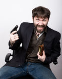 Lustiger bärtiger Mann in einer Jacke und in Jeans, sitzend auf einem Stuhl und halten ein Gewehr Gangsterkonzept Stockfotografie