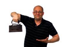 Lustiger überraschter Mann in den Gläsern und in causial Hemd, die altes rostiges Eisen lokalisiert auf Weiß hält Stockbild