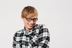 Lustiger blonder hübscher junger Mann, der das zufällige karierte Hemd betrachtet die lächelnde Kamera, Kopienraum, grauer Hinter Lizenzfreies Stockbild