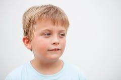 Lustiger blonder Junge, der Kamera betrachtet Stockfoto