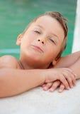 Lustiger blonder Junge im Pool Stockbild
