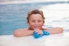 Lustiger blonder Junge im Pool Stockfotografie